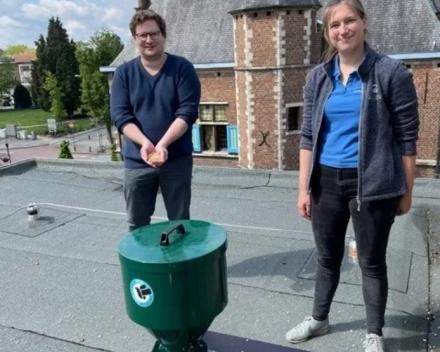Schepen van Dierenwelzijn Bart Lambrecht (N-VA) en Vets For City Pigeons-dierenarts Liesl Van Trappen bij de dispenser op het dak van het Aartselaars gemeentehuis